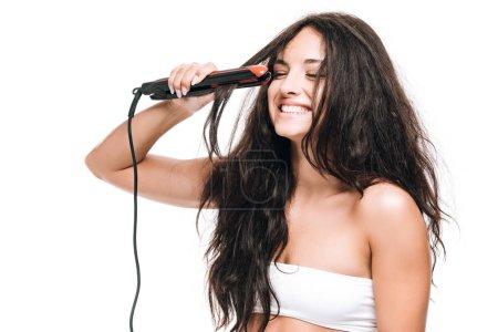 Photo pour Belle femme de brunette souriante coiffant le cheveu bouclé avec le fer plat d'isolement sur le blanc - image libre de droit