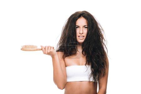 Photo pour Bouleversé brunette belle femme avec ondulé cheveux indisciplinés tenant peigne isolé sur blanc - image libre de droit