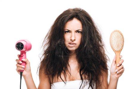 Foto de Morena confusa hermosa mujer peinando el pelo rizado con secador de pelo rosa y peine aislado en blanco - Imagen libre de derechos