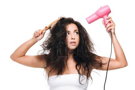 Foto de Morena hermosa mujer peinando el pelo rizado con secador de pelo rosa y peine aislado en blanco - Imagen libre de derechos