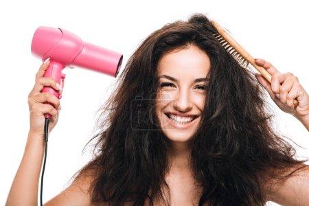 Photo pour Belle femme de brunette souriante coiffant le cheveu bouclé avec le sèche-cheveux rose et peigne d'isolement sur le blanc - image libre de droit