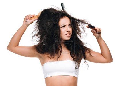 Photo pour Femme inquiète de brunette avec des peignes dans le cheveu ondulé indiscipliné d'isolement sur le blanc - image libre de droit