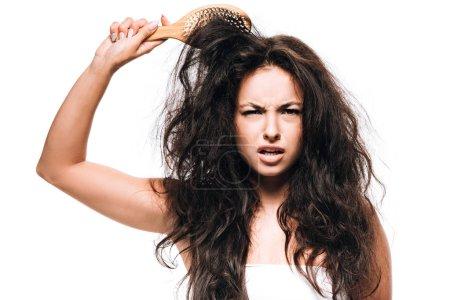 Photo pour Femme brune confus coiffant cheveux bouclés indisciplinés avec brosse à cheveux isolé sur le blanc - image libre de droit