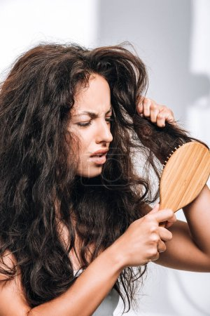Photo for Confused brunette woman styling unruly curly hair with hairbrush - Royalty Free Image