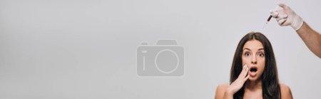 Photo pour Tir panoramique de cosmétologue dans des gants de latex faisant la mésothérapie de cuir chevelu à la belle femme choquée avec de longs cheveux isolés sur le gris - image libre de droit