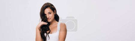 Photo for Panoramic shot of smiling brunette beautiful woman with long healthy and shiny hair isolated on grey - Royalty Free Image