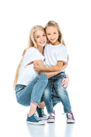 Photo for Happy mother and daughter hugging and looking at camera on white - Royalty Free Image