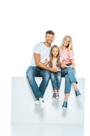 Photo for Happy parents and daughter sitting on cube isolated on white - Royalty Free Image