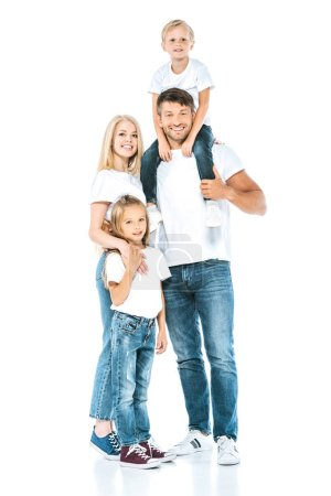 happy father holding son on shoulders near wife and daughter on white