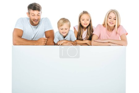 Photo pour Parents et mignons enfants regardant vers le bas près d'une plaque vierge isolés sur blanc - image libre de droit