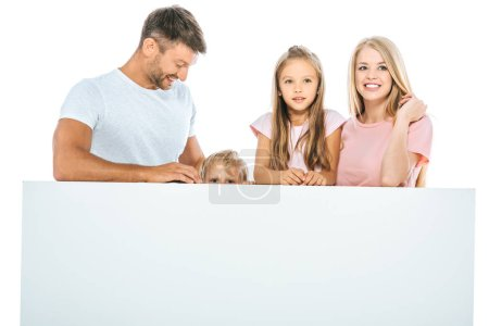 Photo for Happy father looking at son hiding near wife and daughter isolated on white - Royalty Free Image
