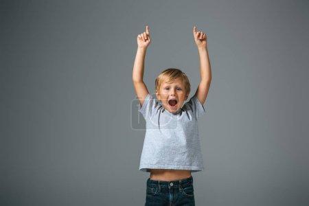 Foto de Jovencito excitado con la boca abierta apuntando con los dedos sobre gris. - Imagen libre de derechos