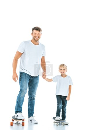 Photo for Happy father holding hands with son and riding penny boards on white - Royalty Free Image