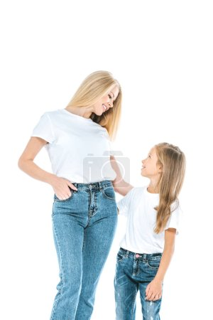 Photo for Beautiful mother standing with hand in pocket near happy daughter isolated on white - Royalty Free Image