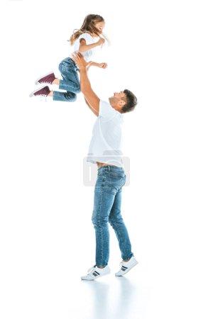 Foto de Padre feliz sosteniendo en armas a su hija mientras se apoya en blanco - Imagen libre de derechos