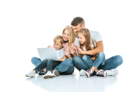 Photo for Positive parents looking at laptop and waving hands with kids on white - Royalty Free Image