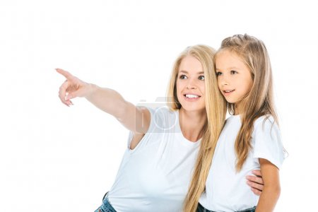 Photo for Happy woman pointing with finger while hugging daughter isolated on white - Royalty Free Image
