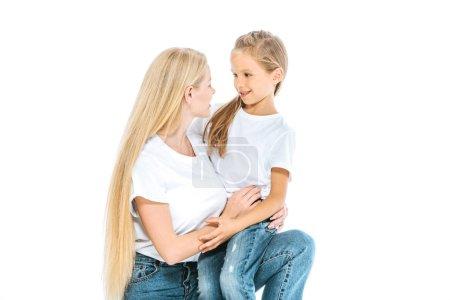 Foto de Madre feliz e hija linda mirando unos a otros aislados en blanco. - Imagen libre de derechos