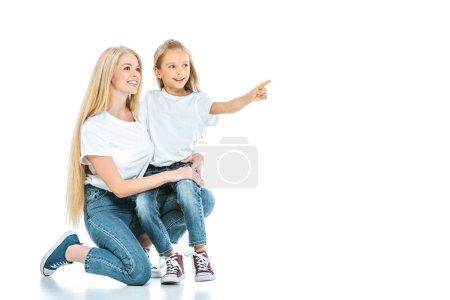 Photo pour Heureuse mère assise près de sa fille pointant du doigt sur le blanc - image libre de droit