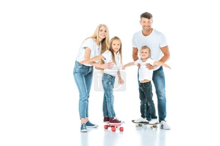 Photo for Happy parents near kids riding penny boards on white - Royalty Free Image