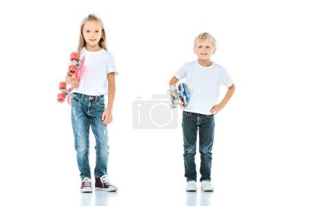 Photo pour Enfants heureux souriant tout en tenant des planches de penny sur blanc - image libre de droit