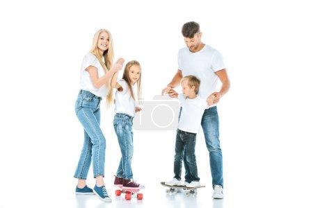 Photo pour Des parents heureux tenant la main d'enfants montant des planches de penny sur des - image libre de droit