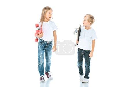 Photo pour Enfants heureux souriant tout en se regardant et tenant des planches de penny sur blanc - image libre de droit