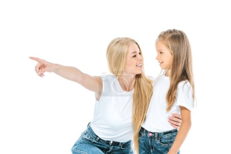 Photo pour Femme heureuse pointant du doigt tout en étreignant mignon enfant isolé sur blanc - image libre de droit