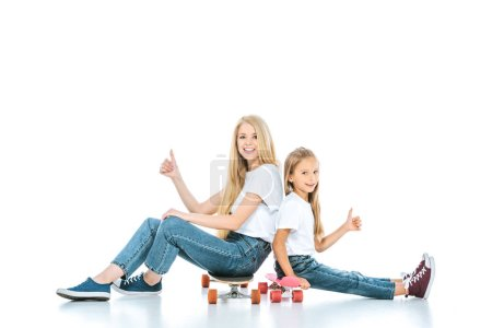 Photo for Happy mother and daughter sitting on penny boards and showing thumbs up on white - Royalty Free Image
