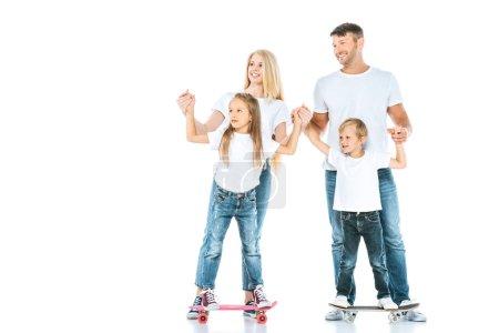 Photo pour Des parents heureux tenant la main de leurs enfants à cheval planches de penny sur blanc - image libre de droit