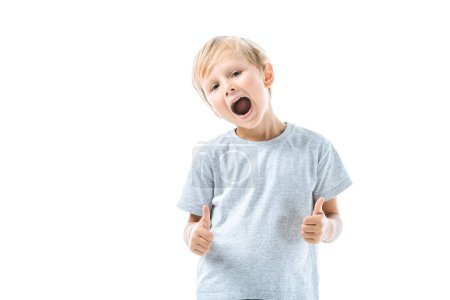 Photo for Excited boy with opened mouth showing thumbs up isolated on white - Royalty Free Image