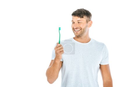 Photo for Cheerful man looking at toothbrush while smiling isolated on white - Royalty Free Image