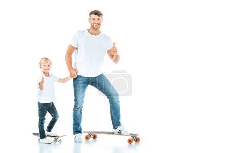 Foto de Padre e hijo felices mostrando pulgares de pie mientras cabalga a bordo peniques aislados en blanco. - Imagen libre de derechos