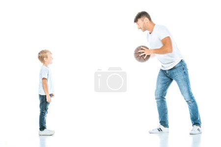 Photo for Happy father holding basketball and looking at cute son on white - Royalty Free Image