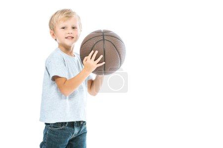 Photo pour Mignon garçon tenant le basket-ball et souriant isolé sur blanc - image libre de droit