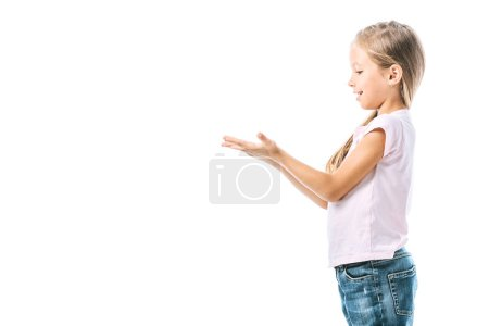 Photo for Side view of positive and cute kid pointing with hands isolated on white - Royalty Free Image