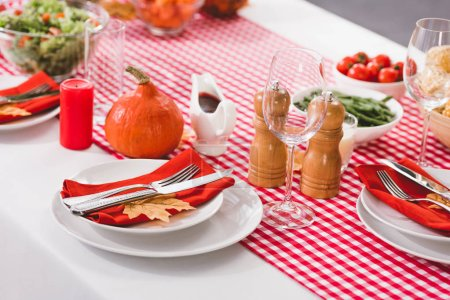 Photo pour Table with plates, glasses, candle, cutlery, pepper mill, salt mill and pumpkin in Thanksgiving day - image libre de droit