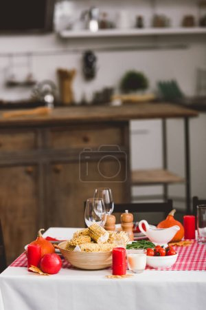 Photo pour Table with cherry tomatoes, glasses, candles, pepper mill, salt mill, corn and pumpkins in Thanksgiving day - image libre de droit
