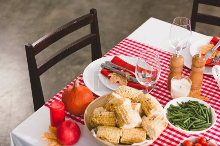 Photo pour High angle view of table with asparagus, glasses, candles, pepper mill, salt mill, corn, plates, cutlery and pumpkin in Thanksgiving day - image libre de droit