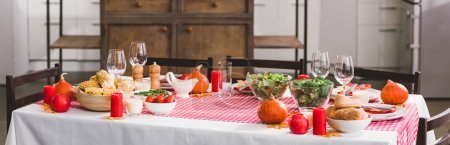 Photo pour Panoramic shot of table with salad, glasses, candles, vegetables, pepper mill, corn, salt mill and pumpkins in Thanksgiving day - image libre de droit