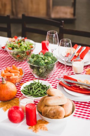 Photo pour High angle view of table with salad, glasses, candles, vegetables, pies, plates and pumpkins in Thanksgiving day - image libre de droit