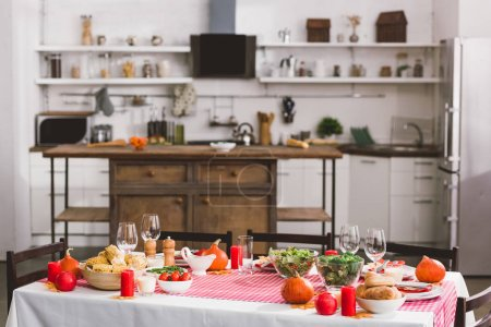 Photo pour Table with salad, glasses, candles, vegetables, pepper mill, corn, salt mill and pumpkins in Thanksgiving day - image libre de droit