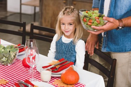 Photo for Cropped view of father holding bowl with salad and cute daughter smiling and looking at camera in Thanksgiving day - Royalty Free Image