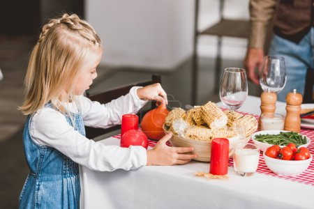 Photo for Selective focus of cute daughter holding bowl with corn and pumpkin in Thanksgiving day - Royalty Free Image