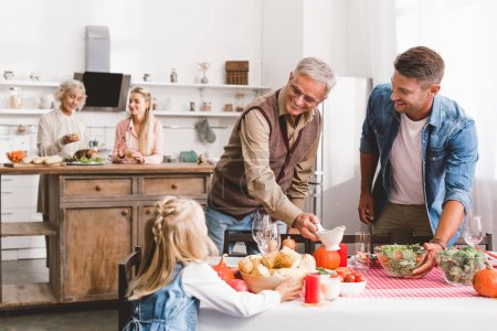 Photo pour Selective focus of smiling father and grandparent looking at kid and setting table in Thanksgiving day - image libre de droit