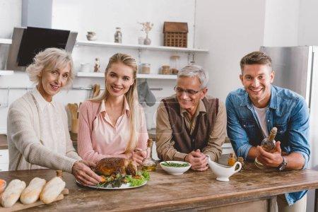 Photo pour Les membres de la famille souriants tenant l'assiette avec la dinde et regardant la caméra le jour de l'Action de grâce - image libre de droit