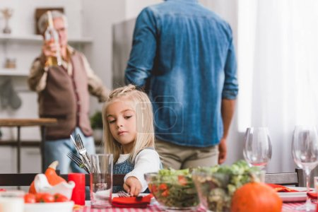 Photo pour Selective focus of cute kid smiling and putting on table cutlery in Thanksgiving day - image libre de droit