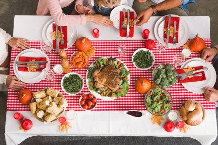 Photo pour Top view of family members sitting at table in Thanksgiving day - image libre de droit