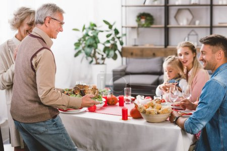 Photo pour Family members sitting at table and grandfather holding plate with turkey in Thanksgiving day - image libre de droit
