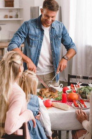 Photo pour Les membres de la famille assis à table et le père coupant de savoureuses dindes le jour de l'Action de grâce - image libre de droit